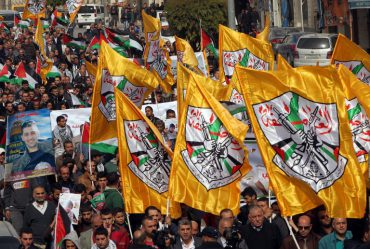 Palestinian demonstrators hold Fatah party flags as they demonstrate in the centre of the West Bank city of Hebron on November 4, 2015 calling for the release of the bodies of Palestinians killed in recent conflict being held by Israeli authorities. The recent violence has claimed the lives of nine Israelis, 70 Palestinians -- around half of them alleged attackers -- and an Arab Israeli since the start of October. AFP PHOTO / HAZEM BADER / AFP / HAZEM BADER