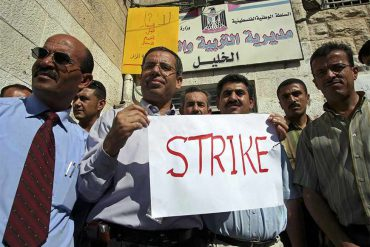 Public school teachers demonstrate in front of a ministry of education office on the first day of the new academic year in the West Bank city of Hebron September 2, 2006. Tens of thousands of Palestinian government employees went on strike in the West Bank and Gaza on Saturday in protest against unpaid salaries and the perceived failings of the Hamas-led government. REUTERS/Nayef Hashlamoun (WEST BANK) - RTR1GWVF