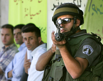 An Israeli border policeman points his gus as he stands guard detaind Palestinian youths during a military operation in the center of Hebron